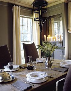 The dining room table looks best set for a casual meal. Wineglasses, bowls, and pewter pitcher are from La Cafetière.