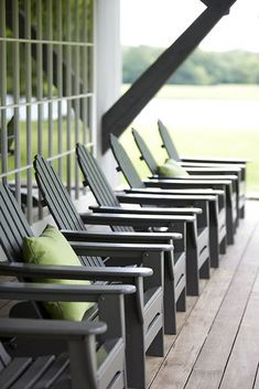 a modern farmhouse/ Adirondack chairs, apple green square pillows, many, many square window panes frame the vast green view . . .
