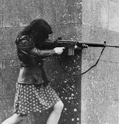 A female IRA fighter armed with an AR-18 taking aim at Pro-British troops during skirmishes. County Armin, Northern Ireland, 1972.
