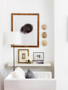 White space with comfy chair, floating shelf, and various framed works of art.