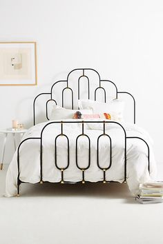 Deco Bed. A thin iron frame makes this piece the perfect spot to display layered quilts, throw blankets and bedding. Its curved silhouette blends deco-inspired motifs with artistically placed pops of brass.