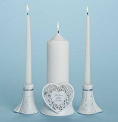 Three piece Unity Candle Holder set includes one pillar and 2 taper candle holders.  The tapers are inspired by the silloheutte of the brides gown.  The pillar features a lattice work heart with the verse, Let Love Light the Way.