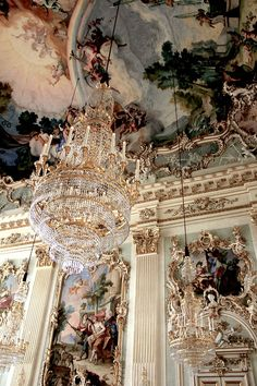 Rococo paneling in white and gold, rich romantic painted ceilings and gold and crystal chandelier