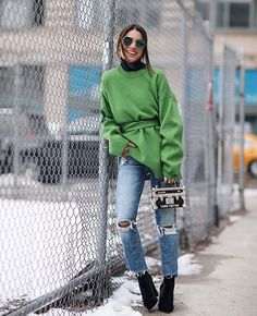 Camila Coelho usa jeans destroyed, moletom oversized sobre turtleneck e skinny boots.