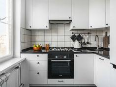 Белая кухонная мебель с черной фурнитурой, стол со столешницей из амбарной доски, хендмейд-декор из натурального дерева – таким увидела свой интерьер хозяйка маленькой кухни в Москве