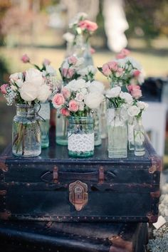 Mason jars of roses and baby's breath, displayed on top of a stack of vintage suitcases. DIY mason jars with lace as wedding decor. Pink and white wedding ideas and inspiration.