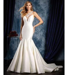 This bold design by Alfred Angelo is perfect for brides that desire a dramatic look with a real Hollywood feel to it. The distinct fishtail shape is unique and creates such a statement and we love the shiny satin material that's been used. Glitzy neckline detail and a sheer overlay were the perfect choices to complete the design and really make it something special.