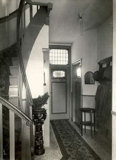 20e Eeuwse bouwstijl. Interieur (hal en trappenhuis) van woonhuis. Kapstok, granieten vloer met loper, op de trap ook een loper. Boven de deuren glas in lood. Nederland, Voorburg, 1930.