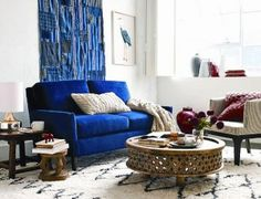 Indigo. This room is anchored by West Elm's indigo Everett loveseat, upholstered in a velvet they call 'ink blue'; indigo interiors go with almost everything
