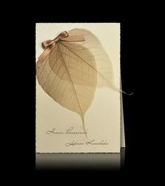 Zaproszenia ślubne D 1209 Zaproszenie w kolorze ecru. Naklejony prawdziwy trawiowy liść z brokatowym połyskiem z ręcznie wykonaną beżową satynową kokardką.