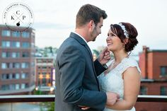 Adorable shot of the happy couple amid rooftops and buildings! Intimate moment in a busy city. Photos by Kate Crabtree Photography #MarryInMaine @portlandregency