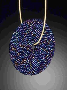 Amy Karash,  Beadwoven torus, gemstone base covered with peyote stitch. Shown in iridescent blue charlotte beads, with 14k cable