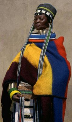 Ndebele Woman in Traditional Dress.    Women of Ndebele people wear brass rings called 'idzila' around their neck, legs, and arms. They begin wearing these when they get married, and the rings are added to by her husband. The more wealthy the husband, the more rings his wife gets. The Ndebele widow will take all her rings off upon her husband's death.