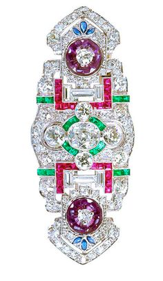 An art deco brooch with a tad more color than usual thanks to the two dainty floral designs made of hand carved petal shaped amethyst. Beautiful calibrated color gems with diamond in platinum brooch with distinct art deco styling. Center diamond cushion of ~1.20 carats. Surrounded by ~4.60 carats of different shaped diamonds, calibrated emerald, ruby & sapphire elements. USA, Art Deco.