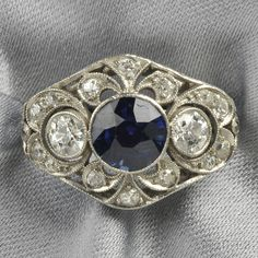Art Deco Platinum, Synthetic Sapphire, and Diamond Ring, bezel-set with a circular-cut synthetic sapphire, further set with old mine- and old European-cut diamonds, millegrain accents