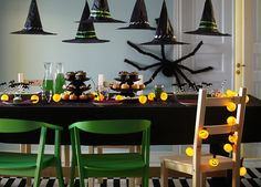 A dining room table decorated with a black fabric table cloth, green plates, glasses, two caraffes and a lighting chain. In front of the table stands two green chairs and one pine chair.