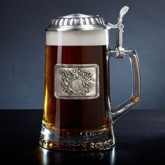 Drink your brew like European royalty with our royal crest personalized beer stein! This handsome stein is crafted from Italian glass with a German-made metal lid. With a personalized initial of your...