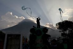 IlPost - Santa Maria de Jesus, Guatemala - Alcuni bambini giocano con degli aquiloni davanti al Volcan del Agua, nel cimitero di Santa Maria de Jesus, in Guatemala, nel giorno della festa dei morti (AP Photo/Moises Castillo)