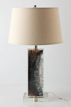 "Scorched Timber Base - Anthropologie.com  DETAILS  Encased in crystal-clear resin, a charred wood branch sits on prominent display, its hues ranging from delicate ash to rich chestnut brown.        Wood, resin      100 watt max      65"" cord      25.5""H, 5""W      Imported"