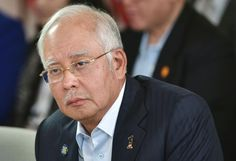 """Two Australian journalists were detained overnight and have been barred from leaving Malaysia after they tried to """"aggressively"""" question Prime Minister Najib Razak about a corruption scandal, police said Sunday.  The pair were detained after they crossed a """"security line and aggressively"""
