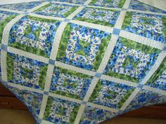 This patchwork quilt has beautiful blue flowers with a touch of purple and green leaves. The colors are wonderful. This quilt will be a lovely addition to any room. This quilt would be great as a lap