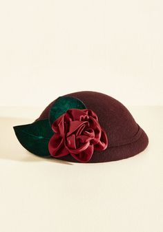 Once you add this burgundy hat to your accessories collection, you'll never want to be without its vintage-inspired style. Crafted from classic wool felt and detailed with textured green leaves and a satiny floral applique, this elegant topper puts a fab look well within reach.