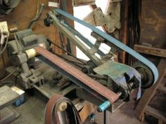 """Homemade 2""""x72"""" belt grinder fabricated from scrap steel and powered by a 2 HP motor."""