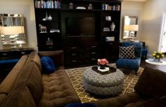 cobalt blue & chocolate brown living room design with Pottery Barn chocolate brown Moorish Tile rug, brown velvet tufted modern sectional sofa, round black storage ottoman, cobalt blue tufted chaise lounge with caster legs, black nightstands chests, beveled mirrors, black media unit cabinet, royal blue round pillow and white & black lattice pillows.