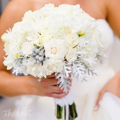 This bouquet consists of all-white roses, peonies, hydrangeas, freesia and rice flower with pops of dusty miller and silver brunia.