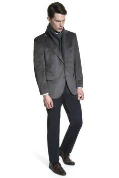 Cachecol chumbo dupla face, sobretudo de lã chumbo padronizado, jeans raw, bota de couro e mala de viagem de nylon com couro.