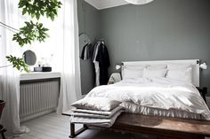 Bedroom in an elegant Malmö home with calming green wall and bench