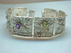 Sterling Silver panel bracelet is pictured with an assortment of amethysts, tourmalines, pearls and opals and also available in all silver and any combination and quantity of gemstones.This Abstract sunburst design bracelet wears comfortably and is definitely an attention getter! NOTE: THIS IS A CUSTOM MADE TO ORDER BRACELET..YOU MUST PLACE AN ORDER WITH YOUR SPECIFICATIONS! This bracelet in sterling silver without gemstones starts at $285. Price increases as gemstones are added...message me…