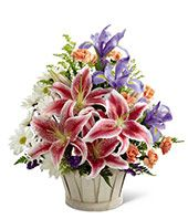 "Peaceful lilies, dahlias, roses, orchids, freesia, hydrangea, carnations, ruscus and salal in a brown willow fireside basket provide beautiful tribute to remember loved ones.  (urn not included). Measures 32""H x 45""W x 21""D.Includes: • Lilies • Roses • Orchids • Hydrangea • Carnations • Florist Arranged, Delivered"