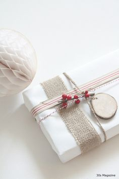 white paper, burlap ribbon, red, and wood slice tag