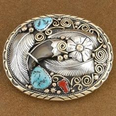 This Bear Claw belt buckle prominently features a genuine bear claw surrounded by hand cut nuggets of number one grade genuine Sleeping Beauty Turquoise and Mediterranean Coral