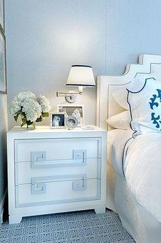 Greek key nightstand, swing arm sconce, hydrangeas, nailhead upholstered headboard, a peak of Leontine Linens on the bed