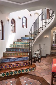 Stunning Spanish tiled spiral staircase with wrought iron banister and terracotta tile floors.
