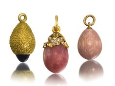 Three Russian egg pendants, St Petersburg, circa 1900-1910, the first enamelled in translucent pink over a textured ground, gold pendant loop, struck with partial maker's mark, possibly _W; the second of swirl-textured gold, the base set with a cabochon sapphire, with illegible maker's mark, possibly _T; the third carved of rhodonite, the shoulder overlaid with a pierced cluster of rose-cut diamond-set flowers, with maker's mark AT, possibly for Alfred Thielemann.