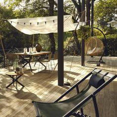 Accumulez des lanternes sur une table pour une jolie ambiance lumineuse sur la terrasse en bois.