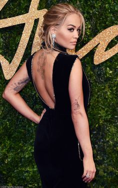 Work it! The rear view of the 24-year-old's frock helped to display her heavily inked frame as she accessorised with diamonds