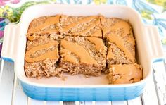 Side view of healthy peanut butter banana baked oatmeal in a square baking dish with a peanut butter drizzle cut into 9 pieces with two removed
