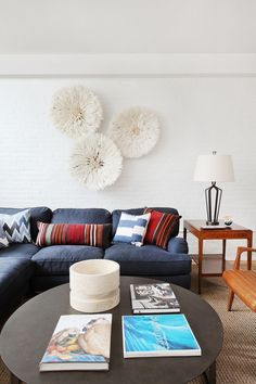 Living space with a well-styled coffee table, juju hats, and a vintage wooden side table
