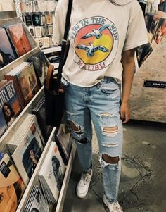 baggy white vintage t-shirt with a colorful graphic print worn with ripped pale blue jeans and white sneakers by a girl standing in a record store The post 1001 Ideas for Celebrating the Return of Grunge Aesthetic appeared first on Jean. Outfit Jeans, Outfit Chic, Baggy Tshirt Outfit, T Shirt Outfits, Outfit With Ripped Jeans, Skinny Jean Outfits, Oversized Shirt Outfit, Pacsun Outfits, Boyfriend Jeans Outfit