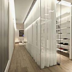 Long white curtains behind glass wall ultramodern walk in closet.