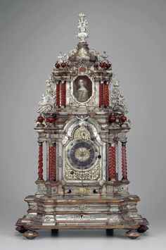 Table Clock with twisted columns and with  a pendulum. Miniature of portrait  of a women in the days of the 1700's. Clockmaker Franz Oschwald Schaffhausen. Wood, covered;: silver plate, gold-plated, Column: ruby glass / Kunckelglas. At 1710 - 1720