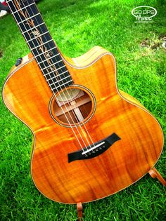 Gorgeous! Taylor Guitars K26ce Hawaiin Koa The K26CE Hawaiian Koa's captivating beauty is matched by a tone that blossoms over time, especially in the midrange.   Comes with Deluxe Brown Taylor Hardshell Case and Taylor Pick, Strap and Stand Bundle at GoDpsMusic.com