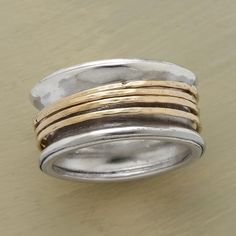 """FOND EMBRACE RING -- Our fond embrace spinner ring is a handmade sterling silver band that embraces four freely moving rings cast of 14kt gold, hammered to sparkle as they spin. Whole and half sizes 5 to 9-1/2. 3/8""""W. This ring is licensed under U.S. patent nos. 6,497,117 and 6,395,732."""
