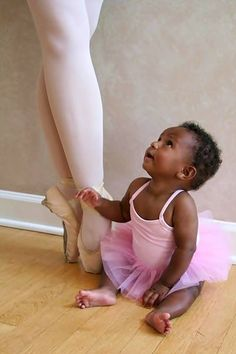 Black Baby Girl, Pretty in Pink leotard and tutu, sitting next to Legs of a Ballet Dancer on Pointe Shoes
