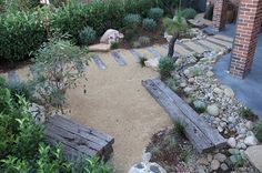 Modern Australian Native Japanese Garden - Waterfall and River/Pond. Materials - Sandstone Boulders, River Pebbles, Recycled railway Sleepers, Crushed Granite, Westringia, Flax, Kangaroo Paw, Blue Fescue Grass
