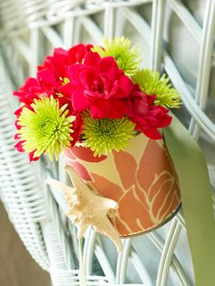 Repurpose a tin can with beach finds. Glue fabric or paper around the clean can. Add desired beach details. To use on a chair back, cut a hole near the top and the bottom of the back of the can, then tie with ribbon threaded through the holes. Or set decorated tin on the table as a centerpiece./